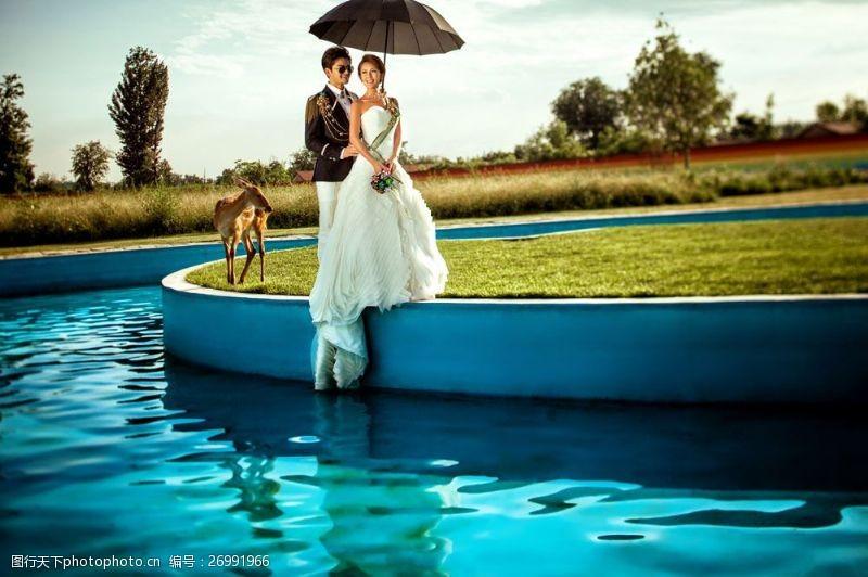 湖水情侣撑伞的婚纱情侣图片