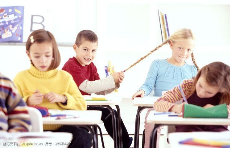 小学生写字拿着小女孩辫子玩耍的小男孩图片