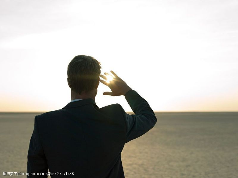 抬手烈日照射的外国商务男人背影图片