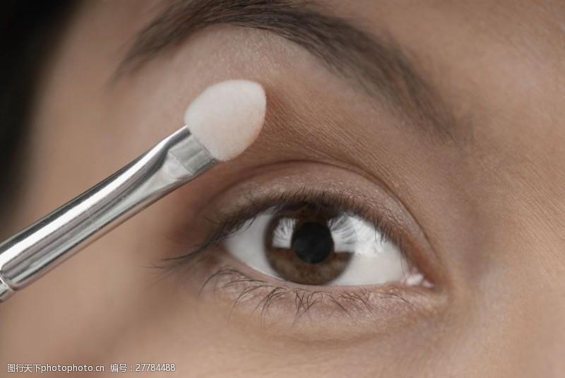 用刷子涂眼影的女人眼部特写图片图片