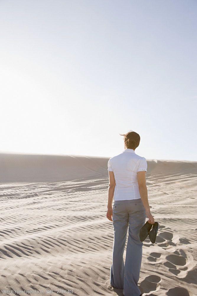 盘头发光脚走在沙漠中的女人背影图片
